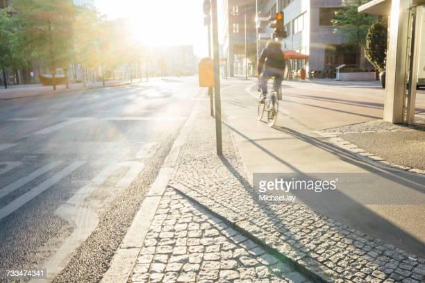 rear view of man riding bicycle on sidewalk during sunny day - gehweg stock-fotos und bilder