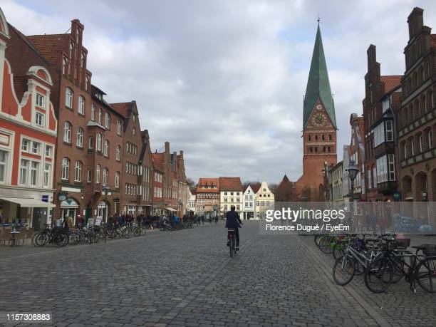rear view of man riding bicycle on street amidst buildings in city - lüneburg stock pictures, royalty-free photos & images