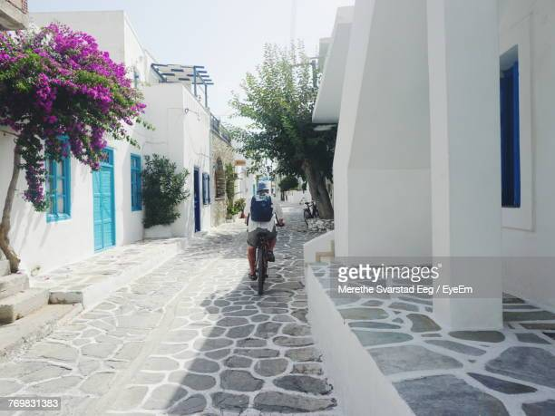 rear view of man riding bicycle on street amidst buildings - whitewashed stock photos and pictures