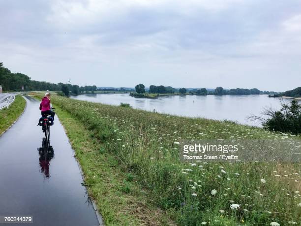 rear view of man riding bicycle on wet road by lake during rainy season - waving gesture stock photos and pictures