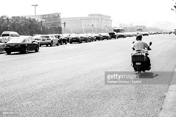 rear view of man riding motor scooter on city street - parham emrouz stock pictures, royalty-free photos & images