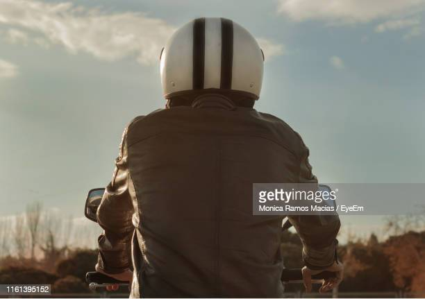 rear view of man riding motorcycle against sky - jacket stock pictures, royalty-free photos & images