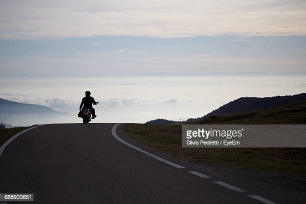 Rear View Of Man Riding Motorcycle On Road Against Sky