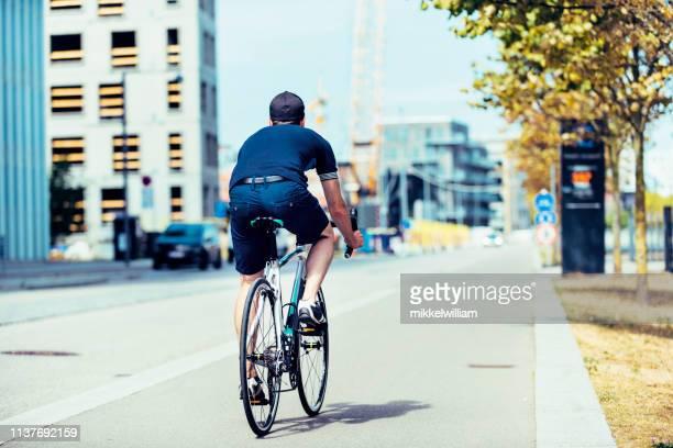 vista trasera de la bicicleta de carreras hombre montando en carril bici en la ciudad - selandia fotografías e imágenes de stock