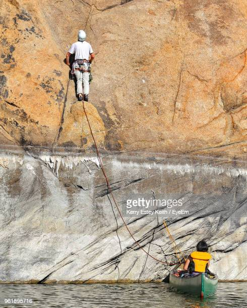 rear view of man rock climbing - kerry estey keith stock photos and pictures