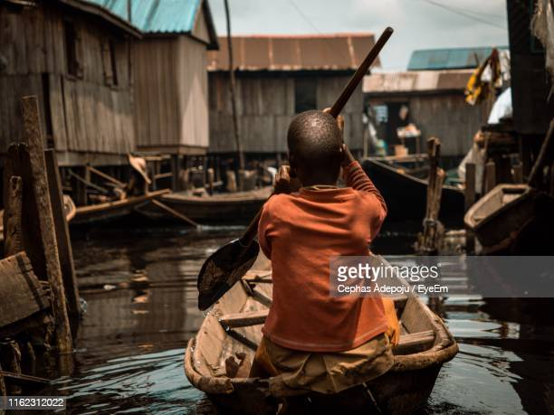 rear view of man rowing boat in lake against houses - lagos nigeria fotografías e imágenes de stock