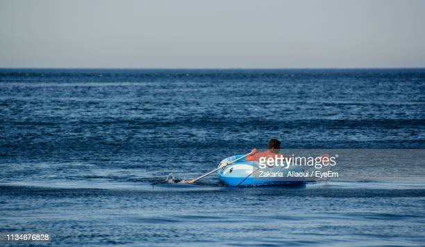rear view of man rowing inflatable raft in sea against clear sky - bote inflável - fotografias e filmes do acervo
