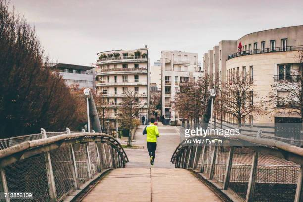 Rear View Of Man Running On Bridge In City