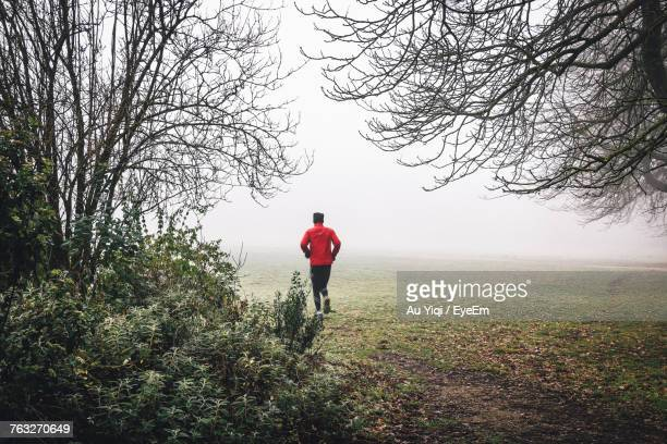 Rear View Of Man Running On Field Against Sky During Foggy Weather