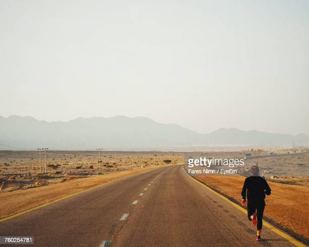Rear View Of Man Running On Road Against Clear Sky