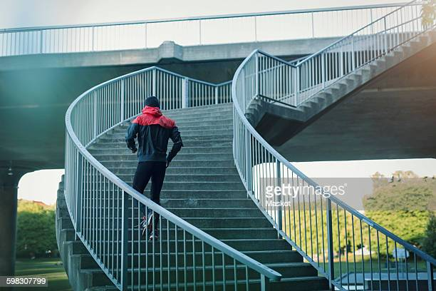 Rear view of man running on staircase