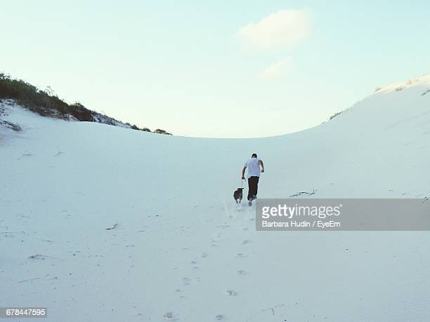 Rear View Of Man Running With Dog On Snow Covered Field Against Sky