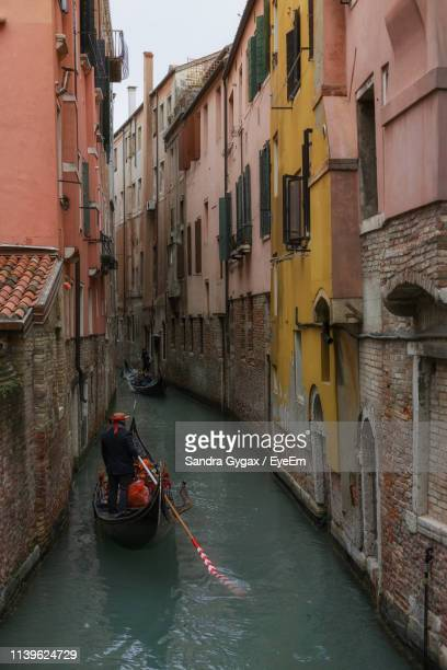 rear view of man sailing boat in canal amidst buildings - sandra gygax stock-fotos und bilder