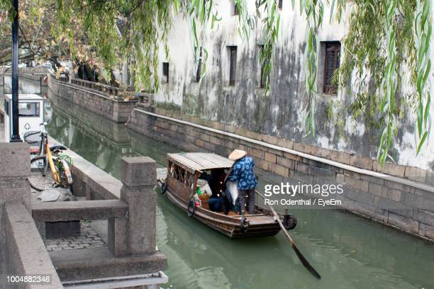 Rear View Of Man Sailing Boat In Canal