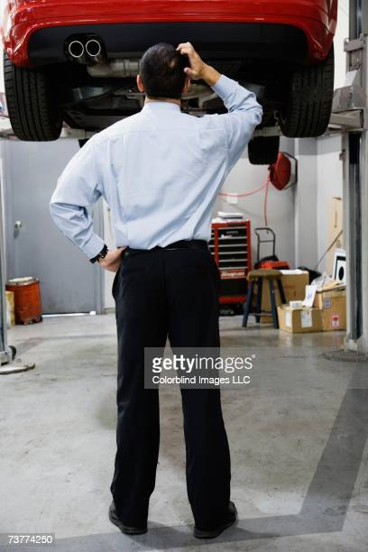 Rear view of man scratching head and looking at car on hydraulic lift