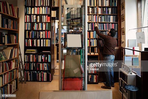 Rear view of man searching book in antique library