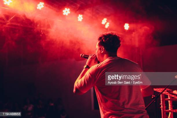 rear view of man singing in music concert - performer stock pictures, royalty-free photos & images
