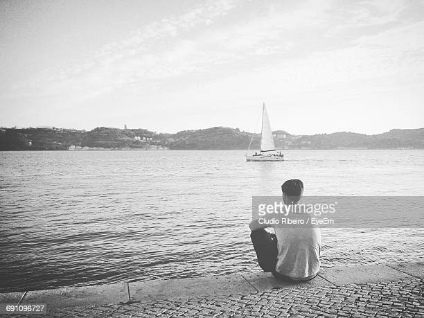 Rear View Of Man Sitting Against Sea
