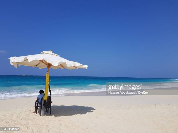 Rear View Of Man Sitting At Beach Against Clear Blue Sky