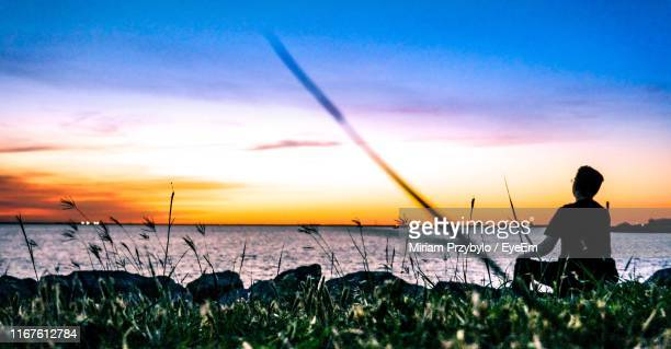 rear view of man sitting at beach against sky during sunset - oklahoma city stock pictures, royalty-free photos & images