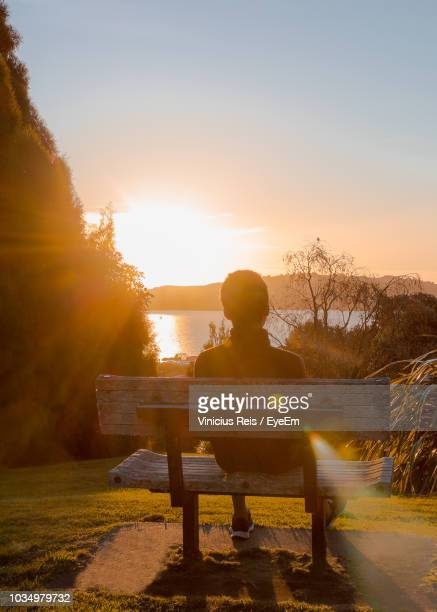 Rear View Of Man Sitting At Park Against Sky During Sunset