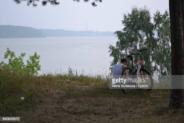 rear view of man sitting by bicycle on field near lake - burlakova stock-fotos und bilder