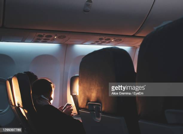 rear view of man sitting in airplane - aeroplane stock pictures, royalty-free photos & images
