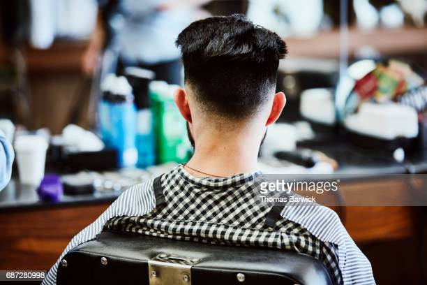 Rear view of man sitting in barbers chair after receiving hair cut