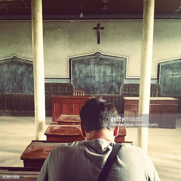 Rear View Of Man Sitting In Bench At Classroom