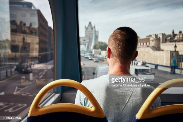 rear view of man sitting in bus - tourist stock pictures, royalty-free photos & images