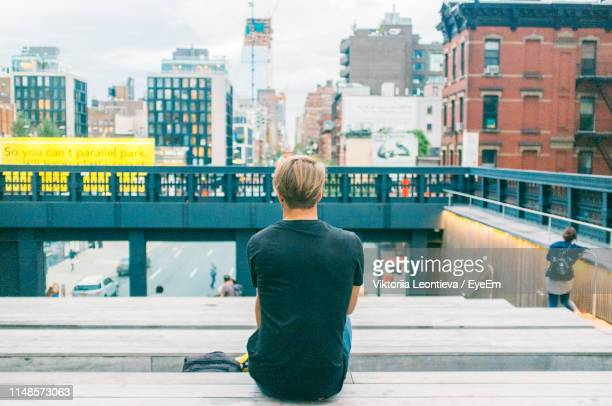 rear view of man sitting in city - man made structure stock pictures, royalty-free photos & images