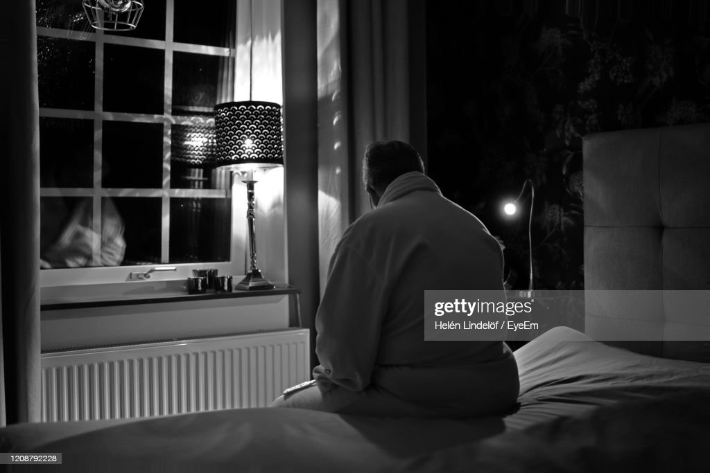 Rear View Of Man Sitting On Bed At Home : Stock Photo