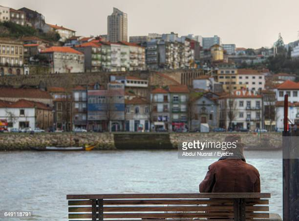 Rear View Of Man Sitting On Bench Against Buildings In City
