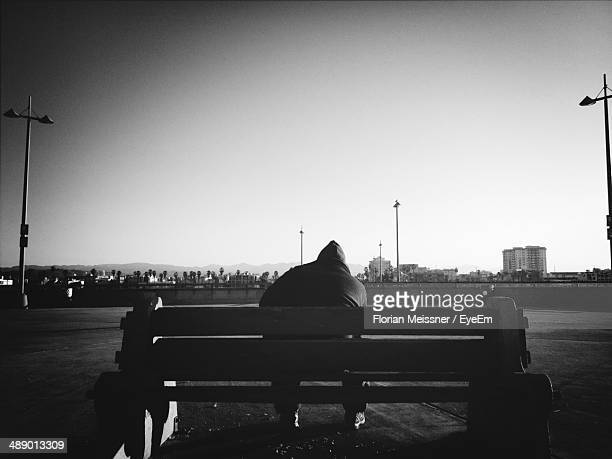 Rear view of man sitting on bench against clear sky