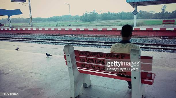 Rear View Of Man Sitting On Bench At Railroad Station Platform