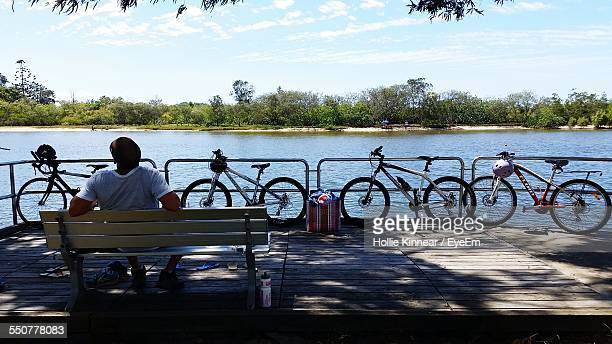 rear view of man sitting on bench in front of parked bicycles against river - flussufer stock-fotos und bilder