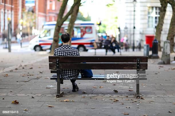 rear view of man sitting on bench on the street - park bench stock pictures, royalty-free photos & images