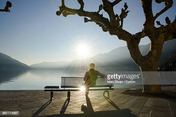 rear view of man sitting on bench while looking at lake against sky during sunset - sitzbank stock-fotos und bilder