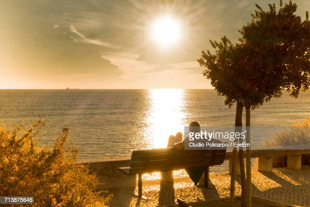 Rear View Of Man Sitting On Bench While Looking At Sunset Over Sea