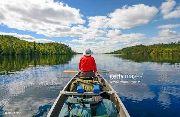 rear view of man sitting on boat in lake against sky - minnesota stock pictures, royalty-free photos & images