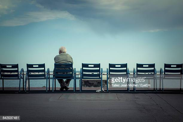 rear view of man sitting on chair against cloudy sky - loneliness stock pictures, royalty-free photos & images