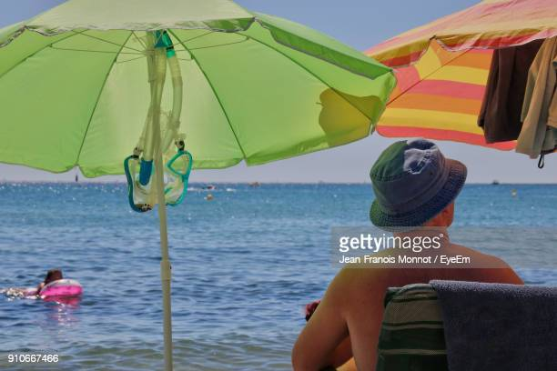 rear view of man sitting on chair at beach - one man only stock pictures, royalty-free photos & images