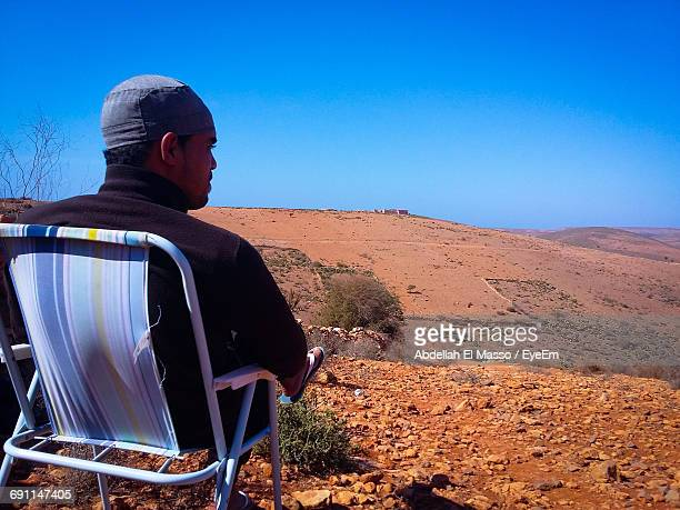 Rear View Of Man Sitting On Chair At Desert Against Clear Blue Sky