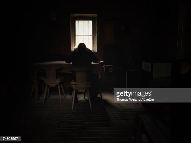 Rear View Of Man Sitting On Chair In Darkroom