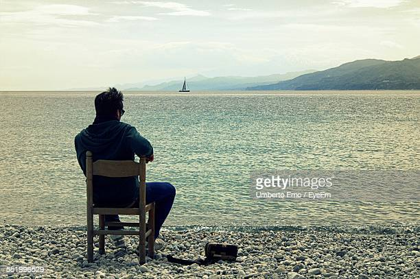 Rear View Of Man Sitting On Chair On Beach