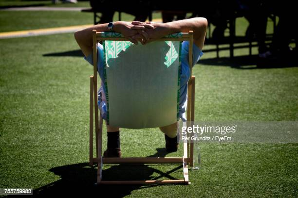 Rear View Of Man Sitting On Chair