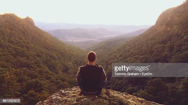 Rear View Of Man Sitting On Cliff Against Mountains At Morans Falls