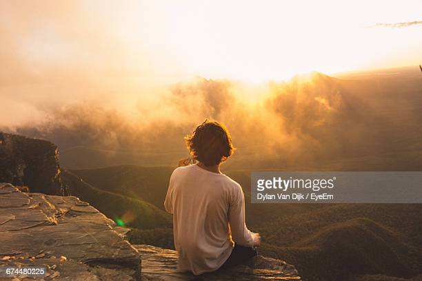 rear view of man sitting on cliff while looking at landscape during sunset - 膝から上の構図 ストックフォトと画像
