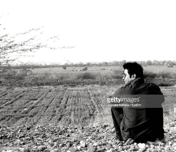 Rear View Of Man Sitting On Field Against Clear Sky