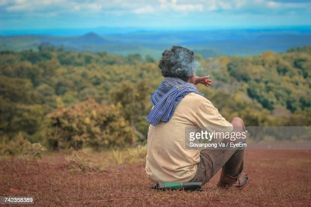 rear view of man sitting on field against sky - 45 49歳 ストックフォトと画像